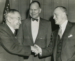Senator Jose P. Laurel shakes hands with U.S. Assistant Secretary of State Walter S. Robertson as James M. Langley smiles in the background. in December 1954